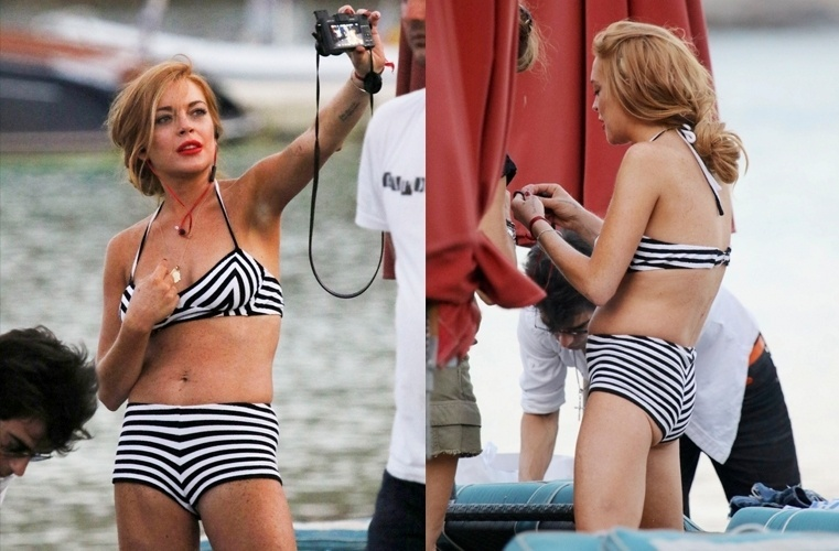 24.jul.2015 - Lindsay Lohan foi clicada aproveitando a praia da Ilha de Míconos, na Grécia, nesta sexta-feira (24). A atriz passa férias no local com amigos e, para o passeio, caprichou no batom vermelho e escolheu um modelo de biquíni maior, que não favoreceu seu bumbum