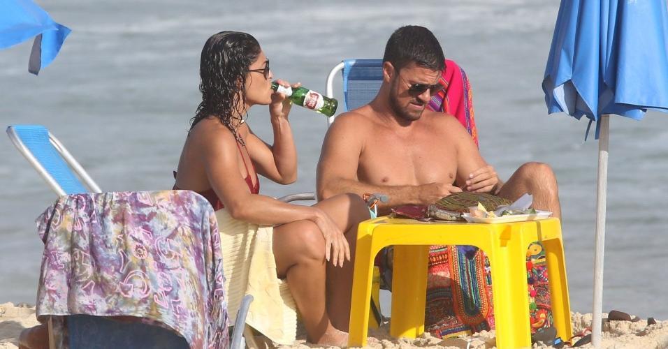 Juliana Paes relaxa na praia e bebe uma cervejinha ao lado do marido, Carlos Eduardo Baptista