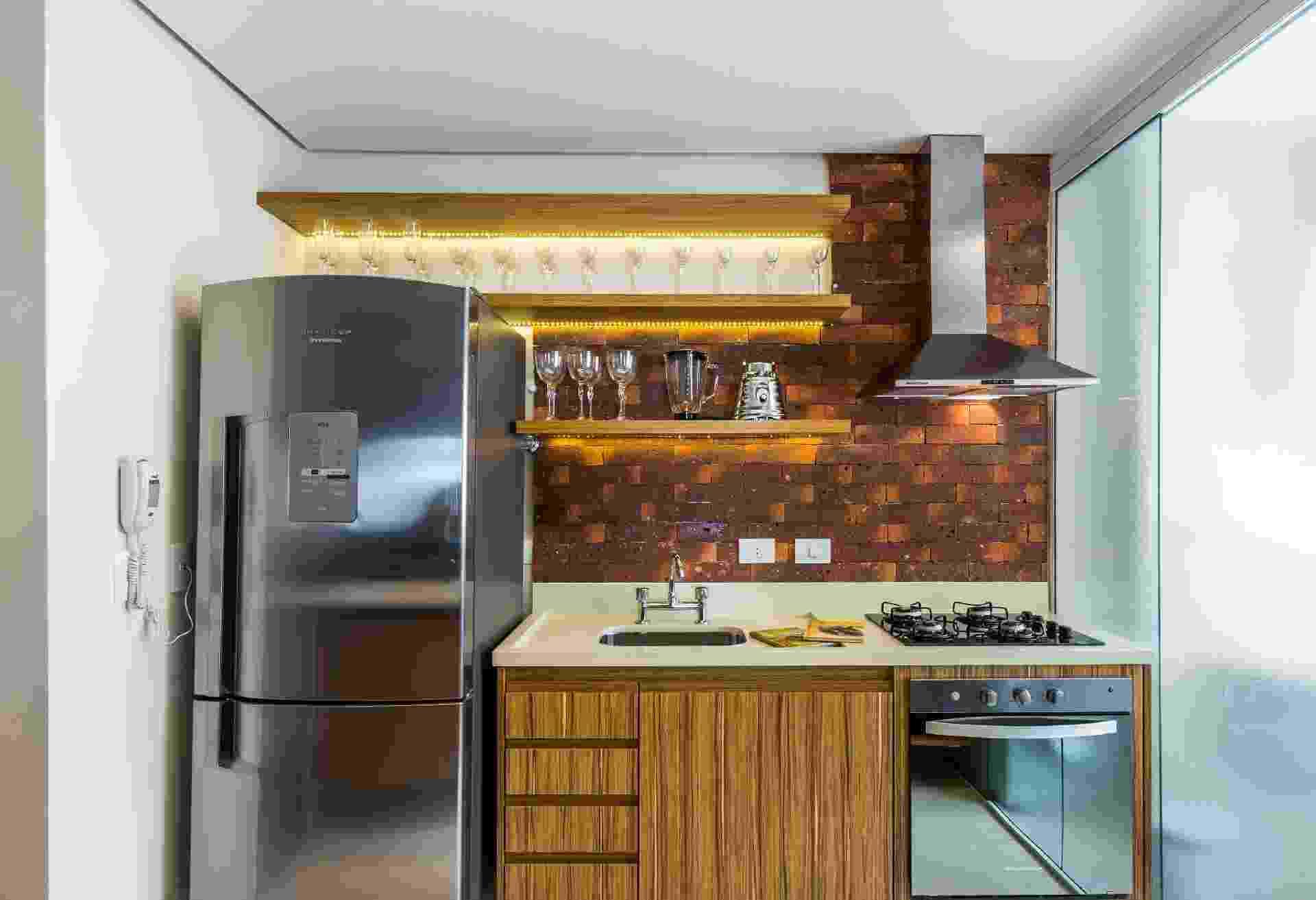 Neste projeto, em vez dos tradicionais armários aéreos sobre o frontão (nome dado à parede sobre a pia), prateleiras com iluminação embutida. O recurso é uma boa pedida para destacar a decoração (aqui taças e eletros de inox) e, somado à marcenaria e ao revestimento rústico, deixou a cozinha mais acolhedora. Projeto BY Arq & Design Arquitetura e Decoração - Melissa Binder/ Divulgação
