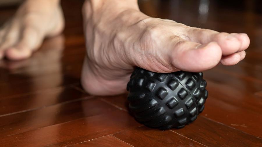 Massagear a região plantar do pé (sola) com uma bolinha pode ajudar a aliviar a dor na região - iStock