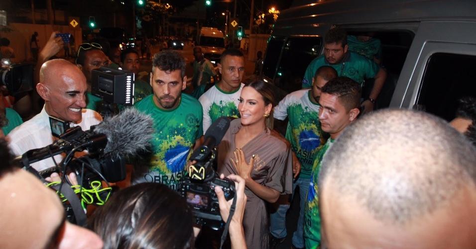 10.jan.2016 - De roupão, Claudia Leitte é cercada por repórteres e integrantes da Mocidade ao chegar para ensaio técnico na Sapucaí