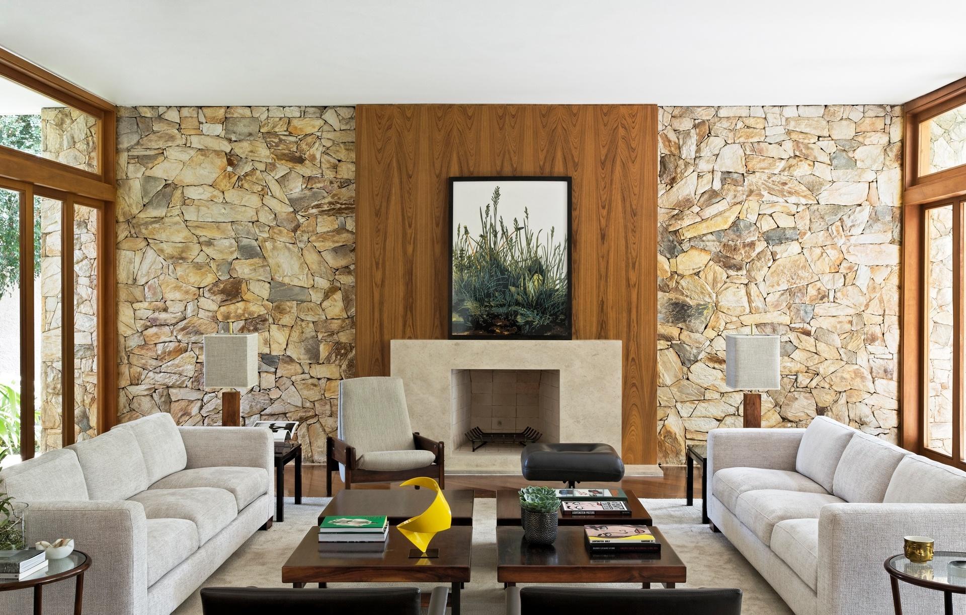 Categoria: Casas Urbanas - Beto Galvez e Nórea de Vitto. A casa da década de 1960 passou por uma reforma, que preservou a parede de pedras atrás da lareira. A paleta de cores sóbrias e versáteis, como o bege e o preto, destaca as obras de arte