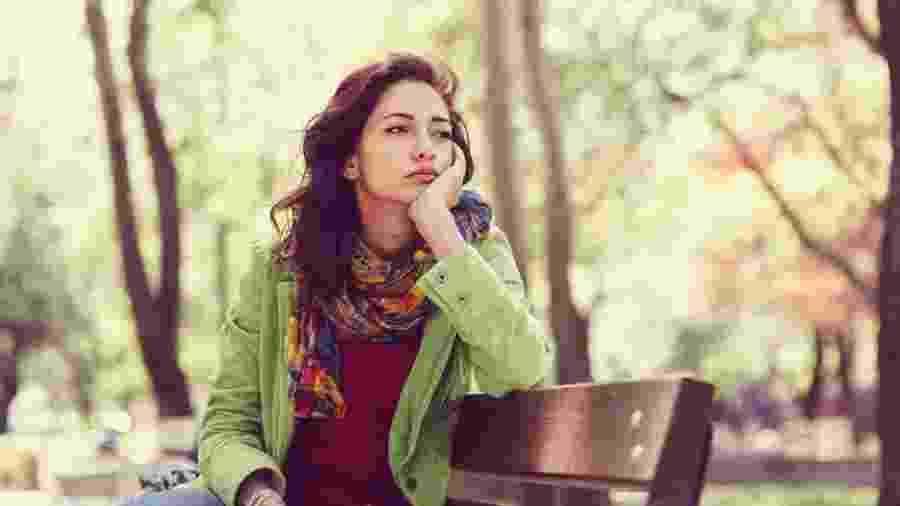 Mulher cansada e triste em banco de praça - iStock