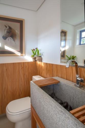O lavabo do espaço de convívio possui ambientação rústica e elegante com destaque para a cuba estruturada com uma caixa de granito contendo seixos rolados e acabamento em madeira laterais. O sítio Marigold é um projeto do arquiteto André Luque