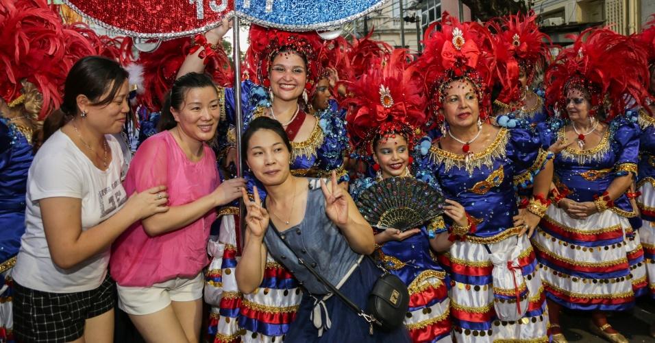 8.fev.2016 - Turistas chinesas fazem foto com integrantes do Bloco da Saudade, nas ruas do Recife