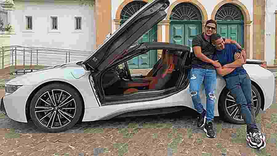 Carlinhos Maia (esq.) e o marido Lucas Guimarães posam ao lado do carrão que custa R$ 700 mil e tem tecnologia híbrida - Reprodução