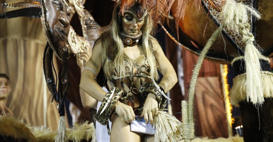 6.fev.2016 - Foliona ajeita seus pertences embaixo da fantasia enquanto aguarda o início do desfile da Unidos do Peruche, no segundo dia de desfiles no Anhembi