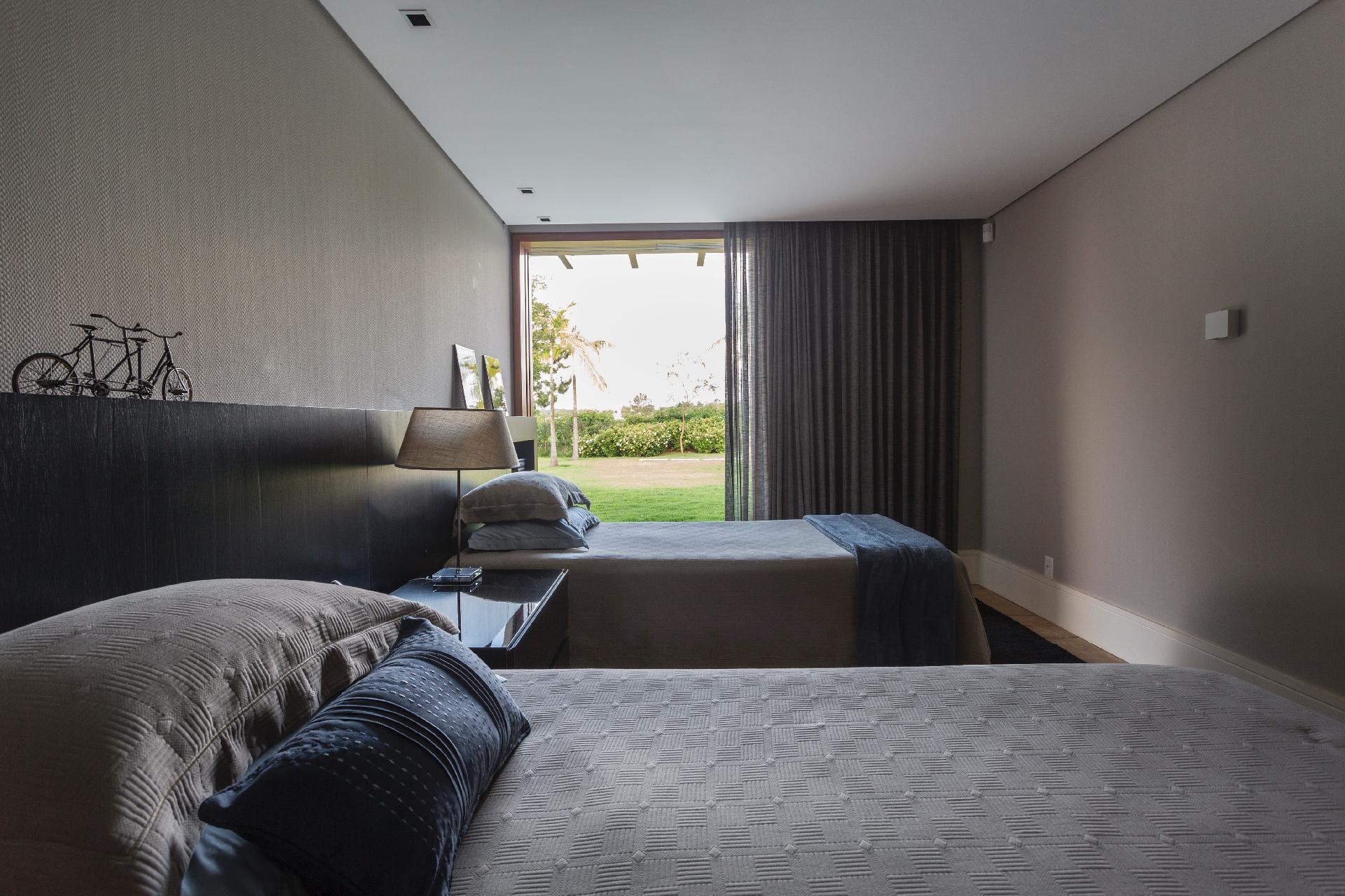 O arquiteto Maurício Karam desenhou uma cabeceira em madeira ebanizada para esta suíte na casa de campo no interior paulista. O dormitório com cortina de linho está conectado ao jardim da residência por uma porta corrediça