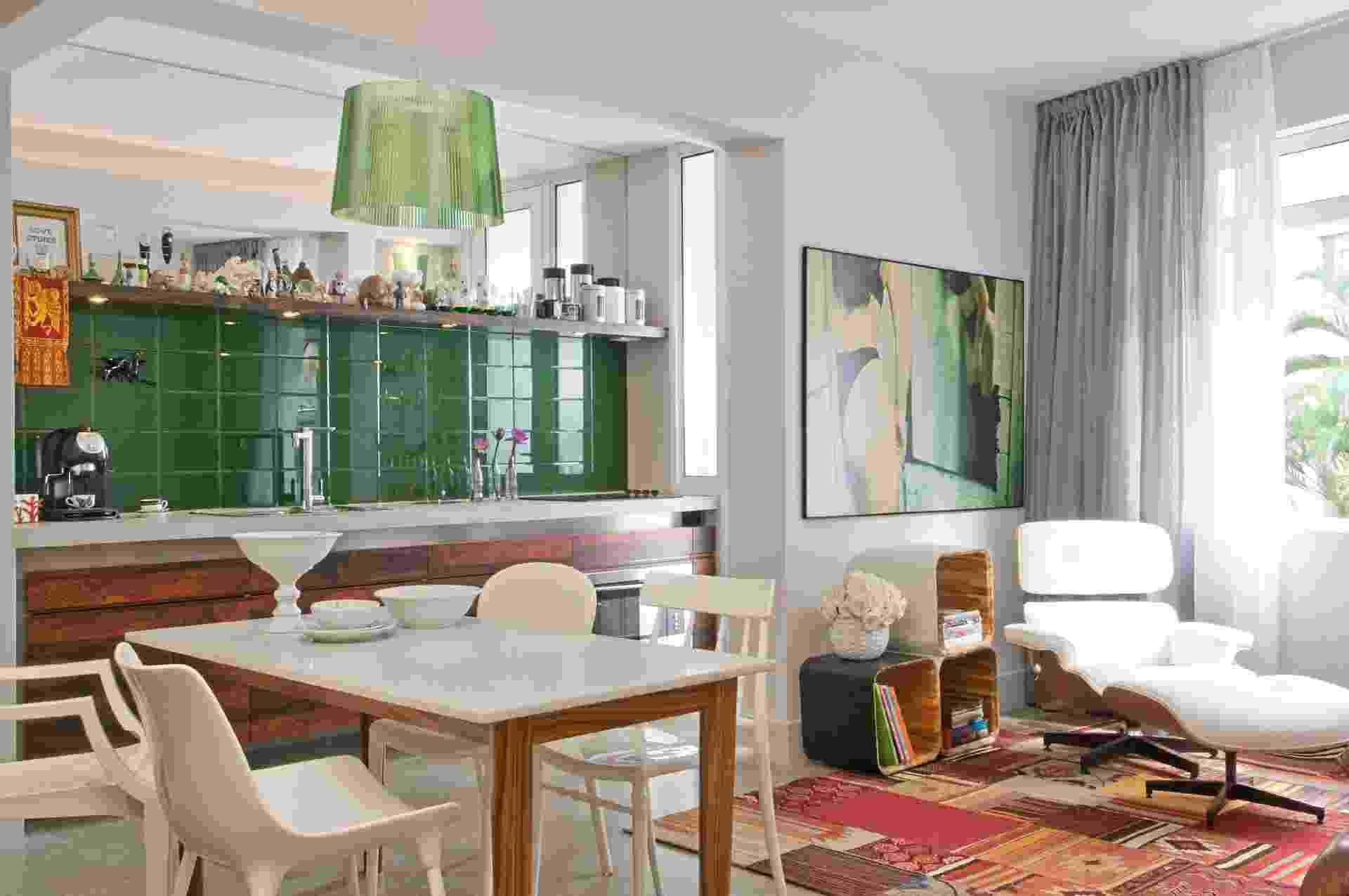 O segredo para acomodar a sala de jantar em espaços pequenos está no planejamento. Neste projeto de Décio Navarro, ela (6,25 m²) está entre a cozinha e o estar, que se integram pelo piso. Feita de madeira e acabamento laqueado no tampo, a mesa compõe com cadeiras de diversos desenhos e as portas do gabinete em laminado padrão jacarandá. O pendente sobre ela combina com o revestimento de parede - Luis Gomes/Divulgação