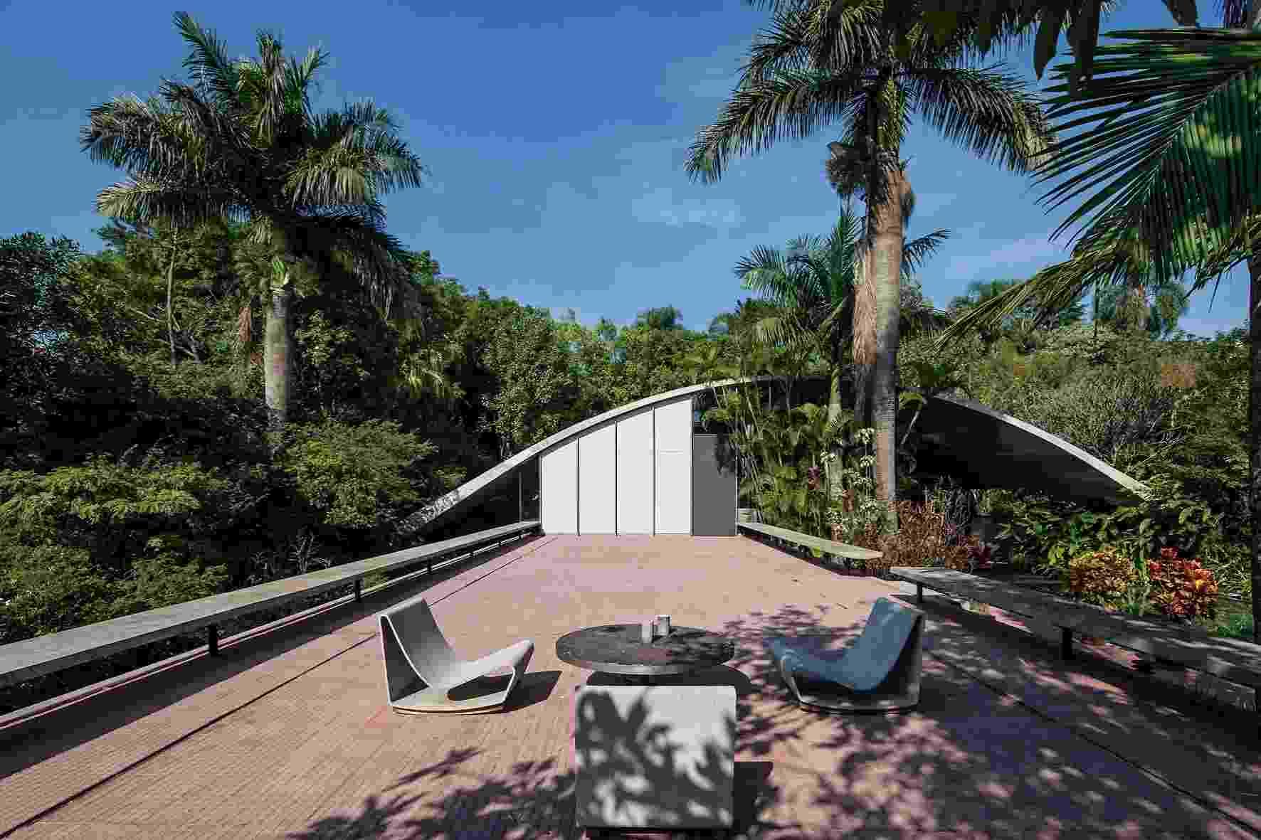A cobertura da Casa Milan, projetada nos anos 70 por Marcos Acayaba, é um arco de concreto armado, como uma fina casca, com isolamento de poliuretano, apoiado nas extremidades do terreno. Uma laje intermediária de concreto armado está sobre doze pilares cilíndricos igualmente espaçados e prolonga-se para o exterior, formando um solarium (foto) onde se encontra o patamar mais alto do terreno (o nível dos dormitórios) - Nelson Kon/ UOL
