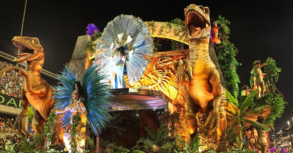 """9.fev.2016 - Alegoria da Portela inspirada no filme """"Jurassic Park"""", a azul e branco enfocou a busca arqueológica de vestígios, rastros e fósseis dos tempos pré-históricos. Nas laterais, integrantes vestidas de arqueólogas eram engolidas por tiranossauros, em um efeito muito divertido"""