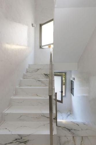 As escadarias da casa Campinas reproduzem o piso da área social, em porcelanato. A pintura recebeu uma camada de cera de carnaúba, para ganhar um efeito brilhante que reflete a luz natural e dispensa o uso de balizadores laterais, ao longo do dia
