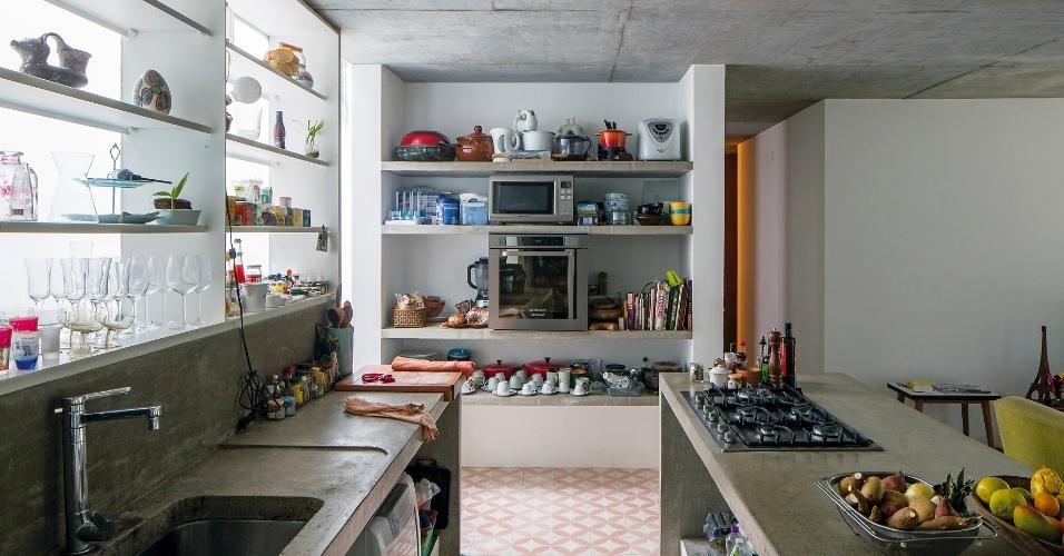 A cozinha da casa LP se separa do living apenas pela ilha de cocção em concreto (à dir.). O ambiente mantém os utensílios, louças, mantimentos e eletrodomésticos à mostra em uma estante metálica (à esq.) ou no nicho com prateleitas. O projeto de arquitetura e interiores é do escritório Metro Arquitetos