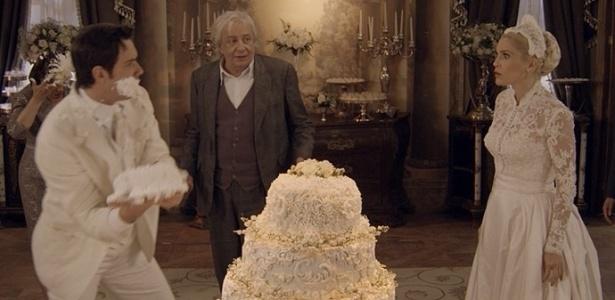 """Pancrácio observa Candinho atirar bolo de casamento em Sandra, abandonada no altar - Reprodução/""""Êta Mundo Bom""""/GShow"""