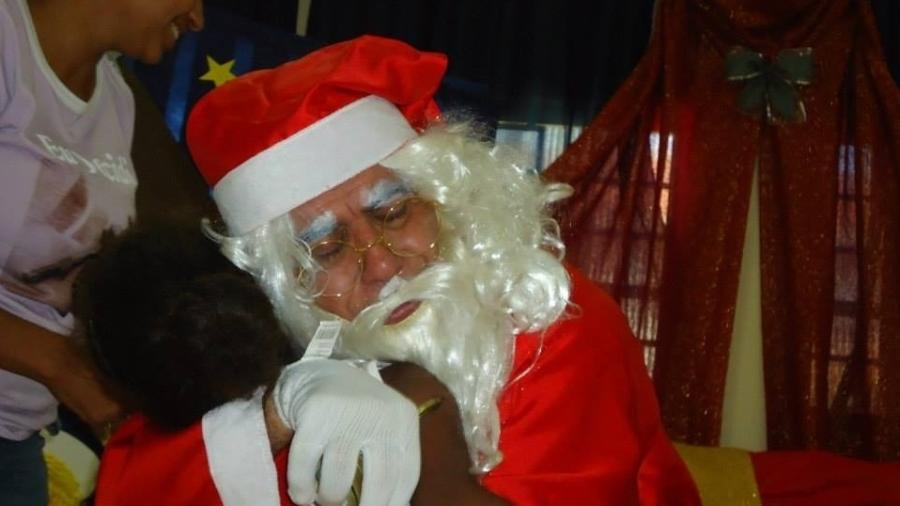 Adilson Ferreira costumava se vestir de Papai Noel para levar sacolas preparadas por padrinhos a crianças. Hoje, a viúva, Marlene, coordena o projeto - Divulgação/Projeto Centopeia