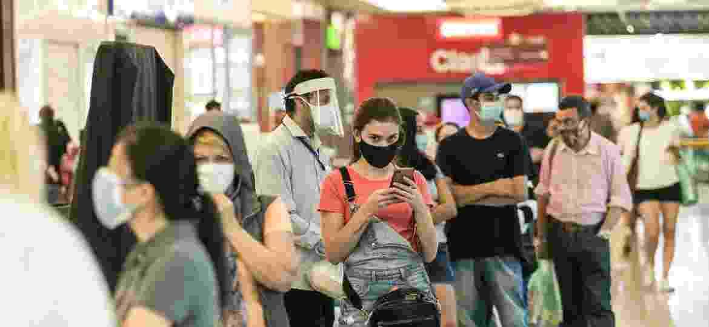 Em fila, de máscara e mantendo certa distância, clientes aguardam a abertura de um shopping na zona oeste de São Paulo - Keiny Andrade/UOL