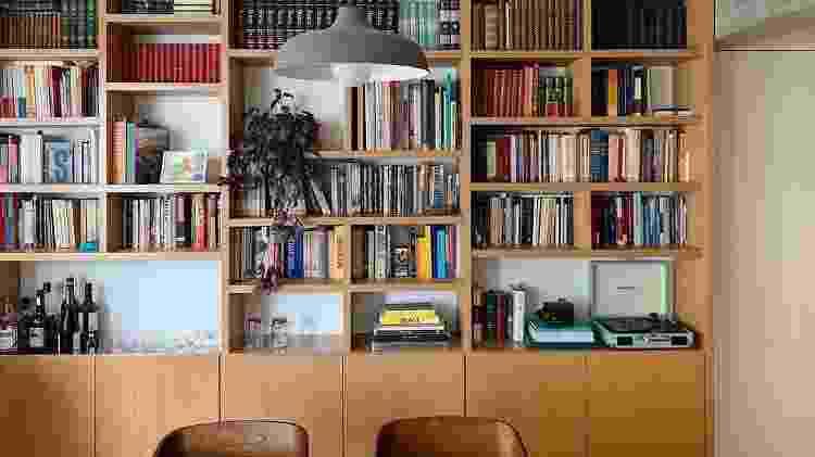 Neste projeto, o @studioterral desenvolveu na marcenaria uma estante na parte superior do móvel, que possuía gabinetes na parte inferior - onde são armazenados as louças desse espaço de jantar - uma área com tampo mais profundo, usado como bar - Divulgação - Divulgação
