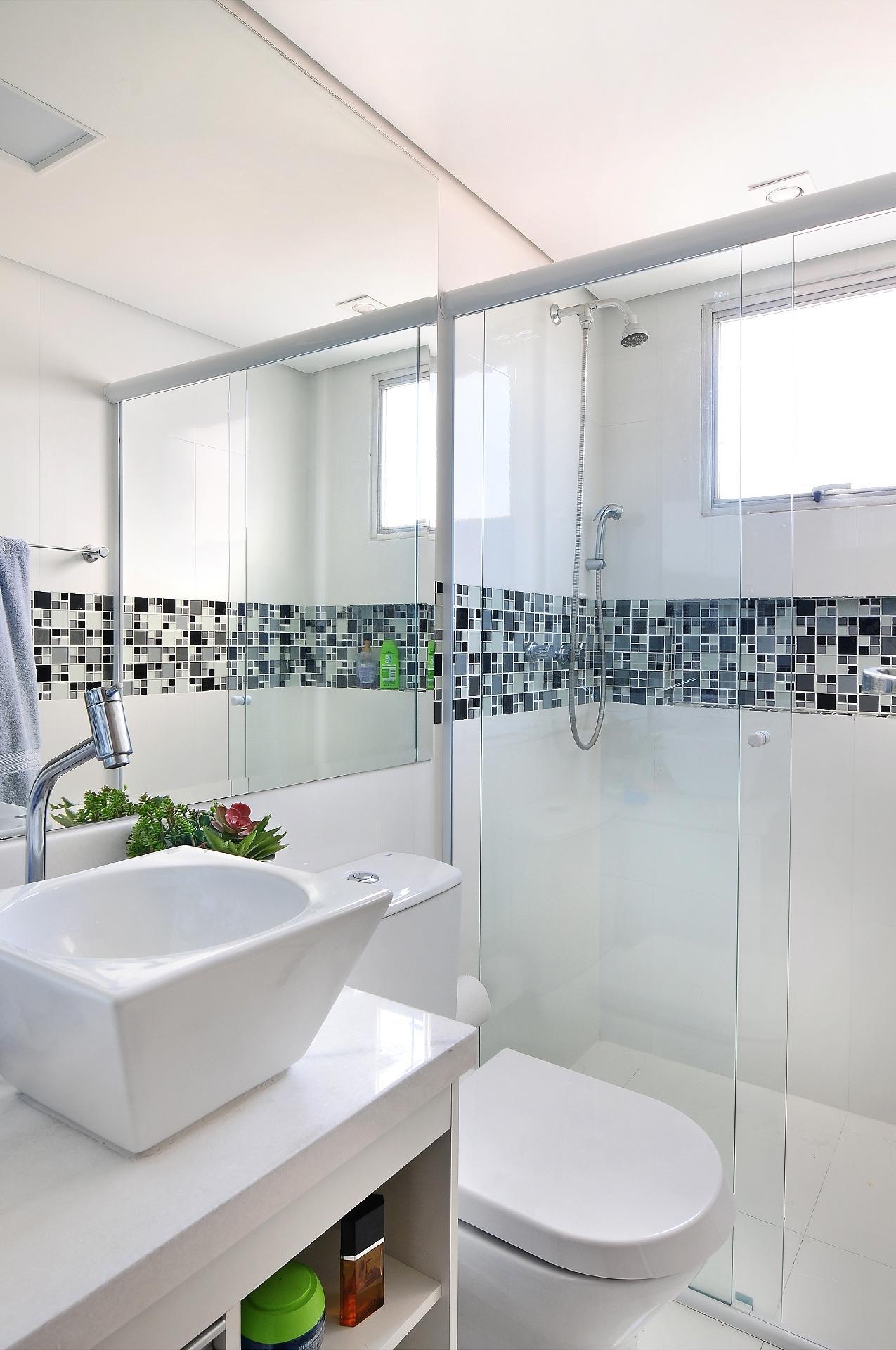 Com a reforma elaborada pelo escritório IBD Arquitetura e Interiores, o banheiro rejuvenesceu: a faixa de pastilhas de vidro disfarça o nicho do xampus e, sobre o fundo branco, torna-se o ponto de destaque do ambiente. O espelho até o teto e o revestimento de porcelanato ampliam visualmente o espaço do apartamento Patch 01, na Cantareira, em São Paulo