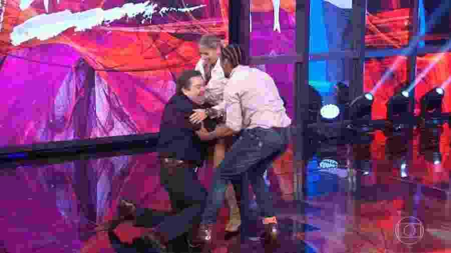 """Após cair de joelhos no palco por conta do abraço de Adriane Galisteu, Faustão ri da situação e chama a amiga de """"trator""""  - Reprodução/TV Globo"""