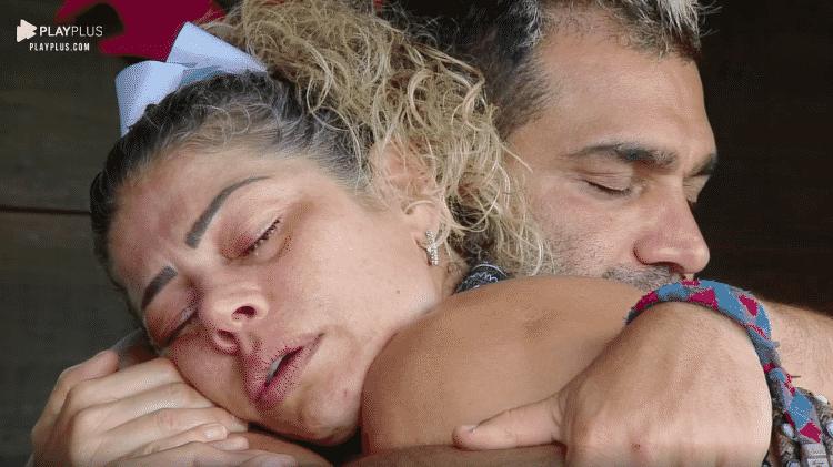 Catia chora nos braços de Evandro, que foi o pivô da polêmica que acabou na sua expulsão do reality show - Reprodução/PlayPlus - Reprodução/PlayPlus