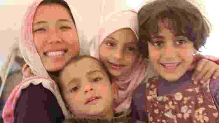 Angelina, à esquerda, posa com crianças em campo de refugiados de Mafraq, na fronteira entre Jordânia e Síria, em 2013 - Arquivo pessoal - Arquivo pessoal