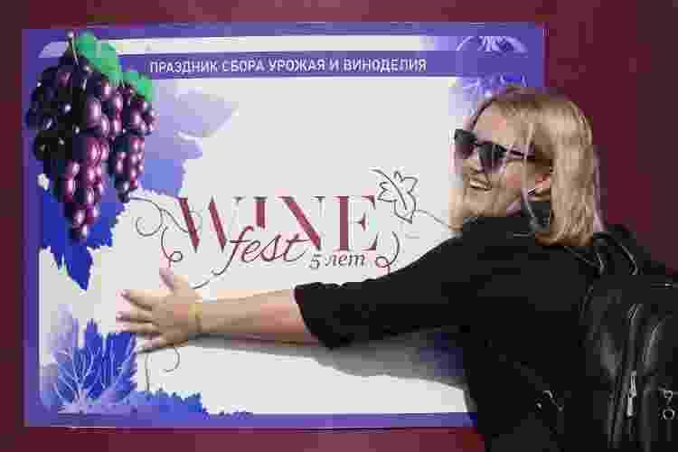 Mulher posa com cartaz do WineFest 2020, na vinícola Zolotaya Balka - Sergei Malgavko\TASS via Getty Images - Sergei Malgavko\TASS via Getty Images