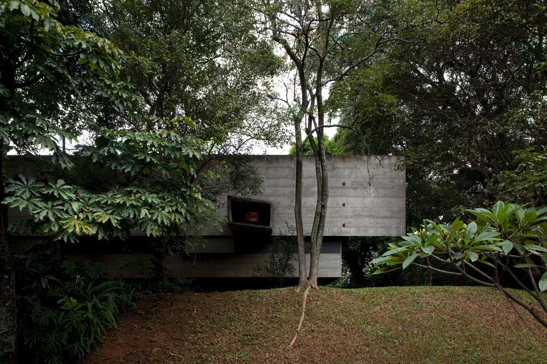 Na fachada lateral se destaca a sobreposição dos volumes de concreto que compõem a casa Butantã, desenhada pelo arquiteto Paulo Mendes da Rocha nos anos 1960. A janela assimétrica permite a entrada de iluminação natural no escritório e é o ponto de atração do olhar