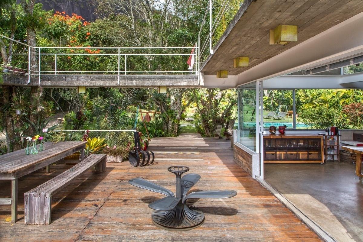 O estar ao ar livre tem ligação direta com a ala social da casa Samambaia, projetada pelo arquiteto Rodrigo Simão. Piscina, árvores de grande porte e montanhas formam o pano de fundo da residência