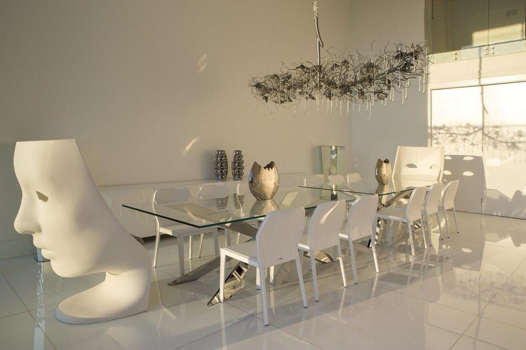 Na sala de jantar desta casa em Campinas (SP) quase tudo é branco. Nas pontas da dupla de mesa de jantar para 14 pessoas estão as poltronas Nemo, desenhadas por Fabio Novembre. O projeto de decoração é do arquiteto Léo Shehtman