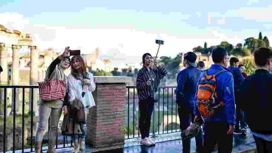 Turistas chineses tiram selfies em frente ao Fórum Romano, em Roma, Itália - Getty Images