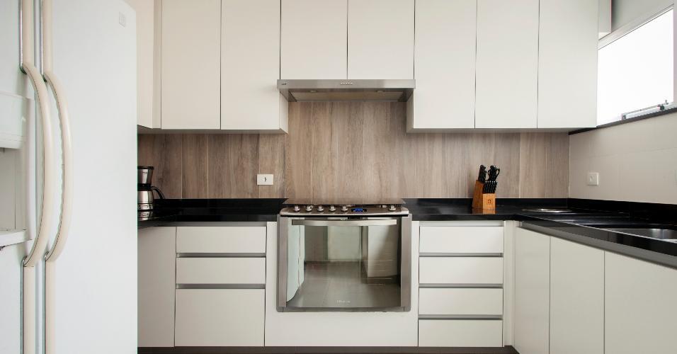 O arquiteto Leonardo Junqueira apostou no branco para fazer a cozinha parecer maior do que ela realmente é.  Em contraste aos revestimentos claros, ele usou porcelanato cinza no piso, granito preto absoluto na bancada e porcelanato imitando madeira de demolição na parede.