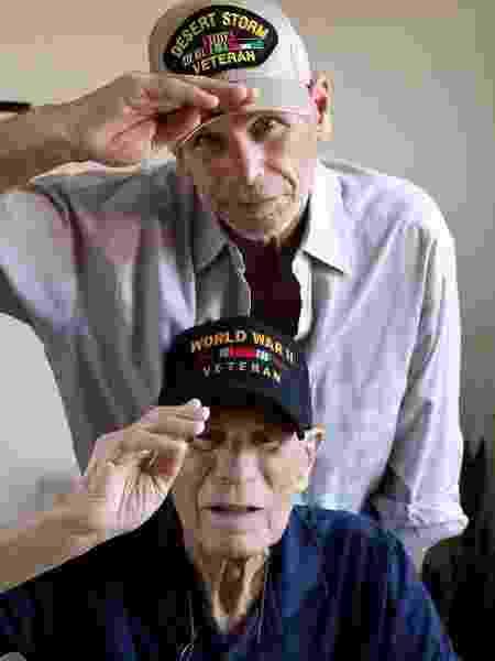 Filho já idoso junto com o pai ainda mais idoso, veteranos de guerra EUA - iStock - iStock