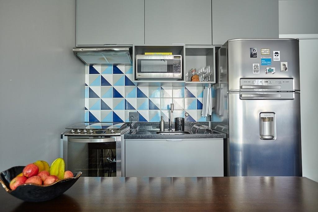 A cozinha é o primeiro ambiente do apê com 29 m² reformado pelo escritório Notar Design, em Pinheiros, na zona oeste de São Paulo. Ao lado da porta de entrada está uma parede revestida com azulejos decorados. Feitos sob medida, os armários acoplam os eletrodomésticos e a bancada de trabalho com pia. Note que o aço escovado combina com o cinza das peças, sem contrastar