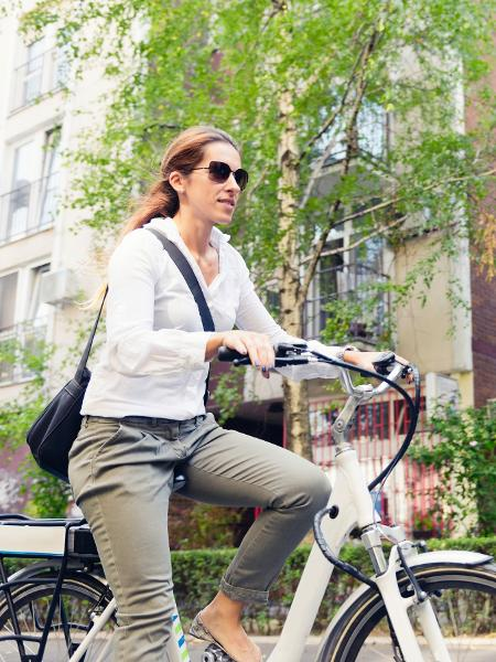Mulher andando de bicicleta elétrica - iStock