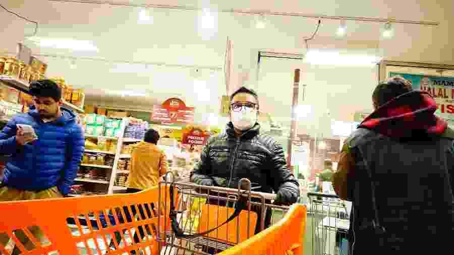 Homem faz comprar em supermercado de Nova York usando máscara de proteção contra o coronavírus - Getty Images