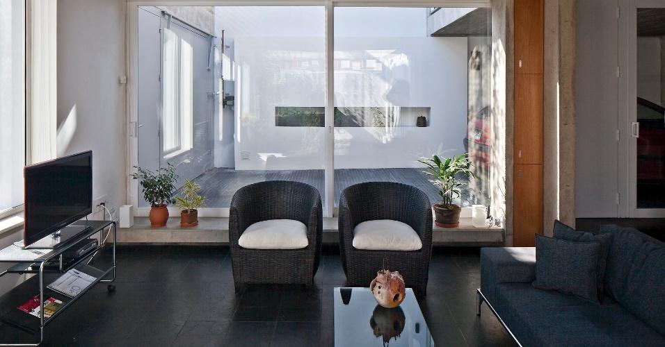 O acesso principal da casa Ibiray se faz pela garagem (ao fundo e à esquerda), que fica separada do living por esquadrias de alumínio envidraçadas. O estar é o único ambiente interno do térreo não recuado em relação à fachada, no projeto de Lucho Oreggioni e Sonia Prieto
