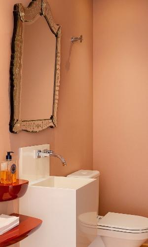 Para renovar o lavabo deste apartamento, Daniela Cianciaruso e Ricardo Caminada, da Díptico Design de Interiores, pintaram a parede num tom roseado e mudaram o espelho. O modelo veneziano virou a atração do ambiente e nem foi preciso mudar o piso de madeira