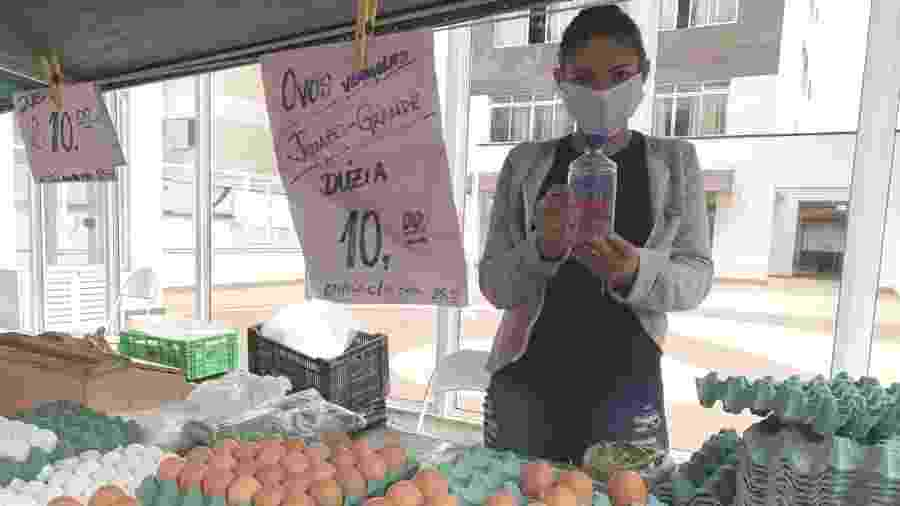 Feirante Cláudia de Jesus, 26, munida de máscara e álcool gel - Janaina Garcia/UOL