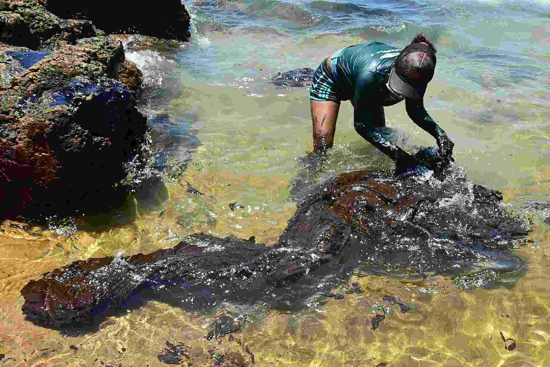Voluntários e operários fazem limpeza de mancha de óleo que chegam às praias de Itapuama e praia de Xareu em Cabo de Santo Agostinho, litoral sul de Pernambuco, nesta segunda-feira (21) - Ademar Filho/Futura Press