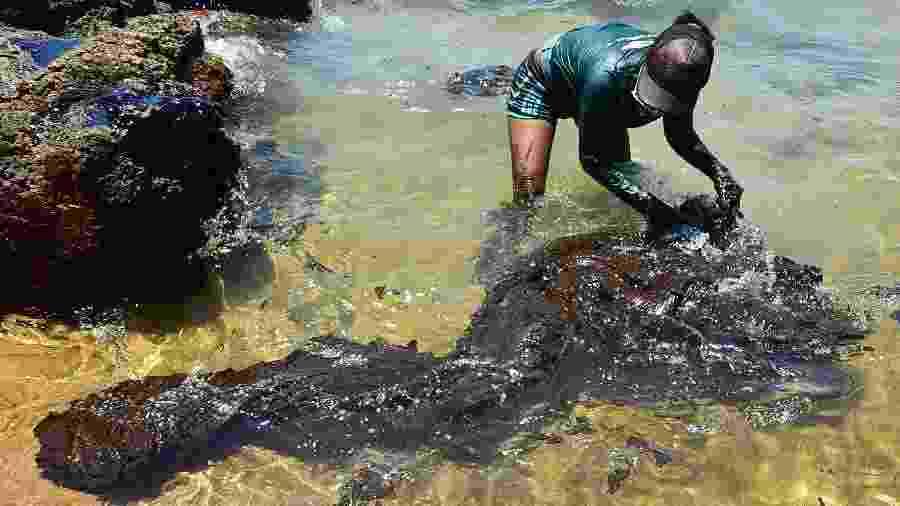 Voluntários e operários limpam mancha de óleo nas praias de Itapuama e Xareu, no litoral sul de Pernambuco - Ademar Filho/Futura Press