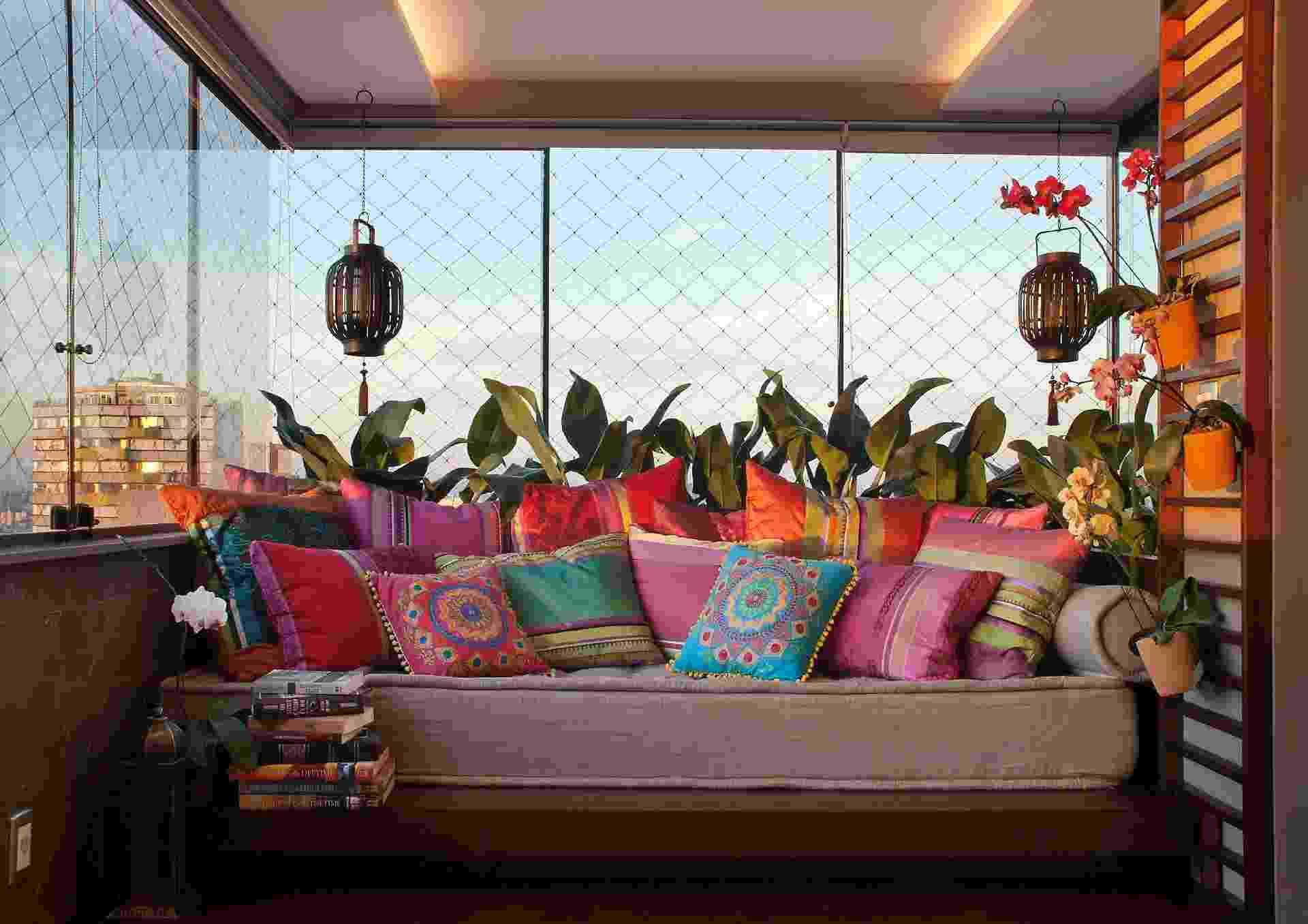 Este canto de uma sacada de 12 m2 foi idealizado pelo arquiteto Luciano Teston para a pratica de ioga, leitura ou momentos de intimidade. O tablado de imbuia que é acessado por degraus acomoda um futton de linho recoberto de almofadas ultracoloridas. O painel ripado com vasos com orquídeas funcionam como um mini jardim - Sérgio Vergara/Divulgação