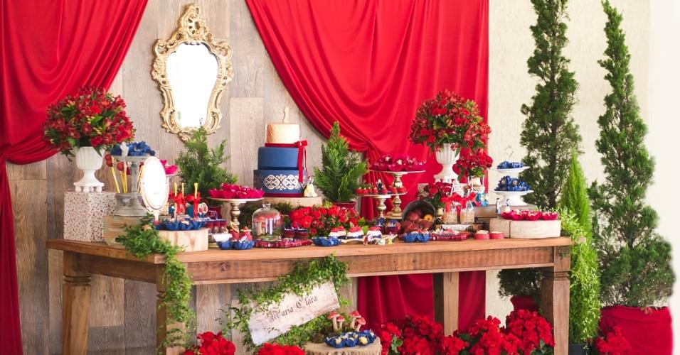 Visão geral da mesa do Parabéns do aniversário de um ano de Maria Clara, inspirado em Branca de Neve. Por todos os lados, havia referências ao tema, como o espelho da Rainha Má, as maçãs e muitas plantas representando a floresta encantada
