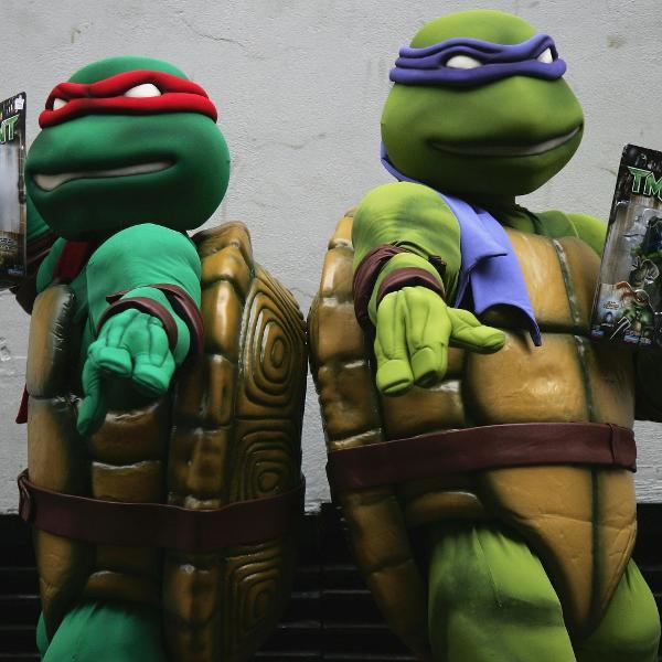 """Pessoas fantasiadas de """"Tartarugas Ninja"""" seguram bonecos dos personagens"""