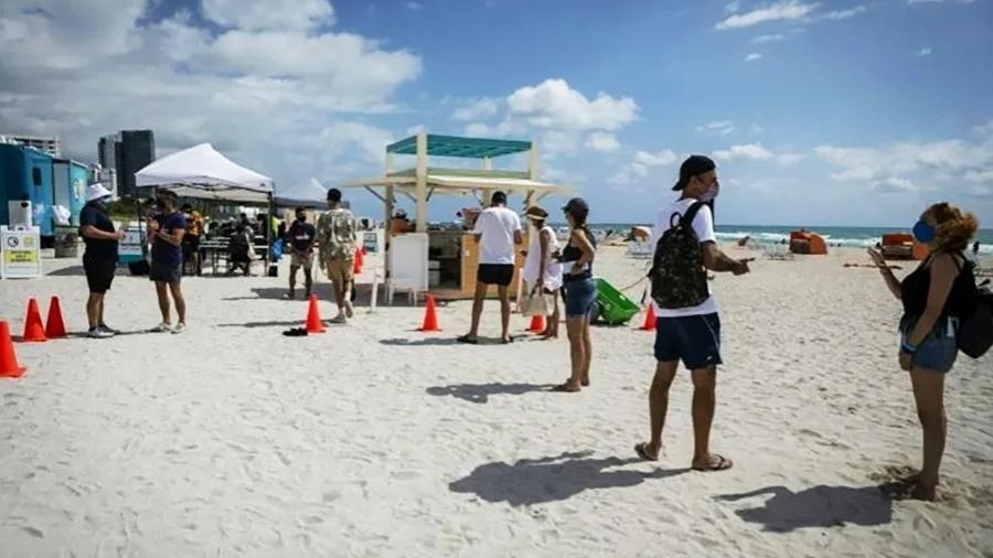 As pessoas esperaram em uma fila constante, mas rápida, pela vacina da Johnson & Johnson na praia de South Beach. - AFP