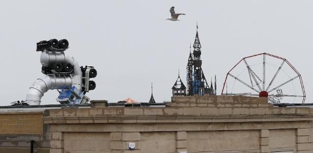 Uma espécie de parque de diversões à beira-mar é visto em Weston-super-Mare, no sudoeste da Inglaterra; segundo a mídia local, a criação é um parque temático distópico idealizado pelo artista urbano Banksy - Suzanne Plunkett/Reuters