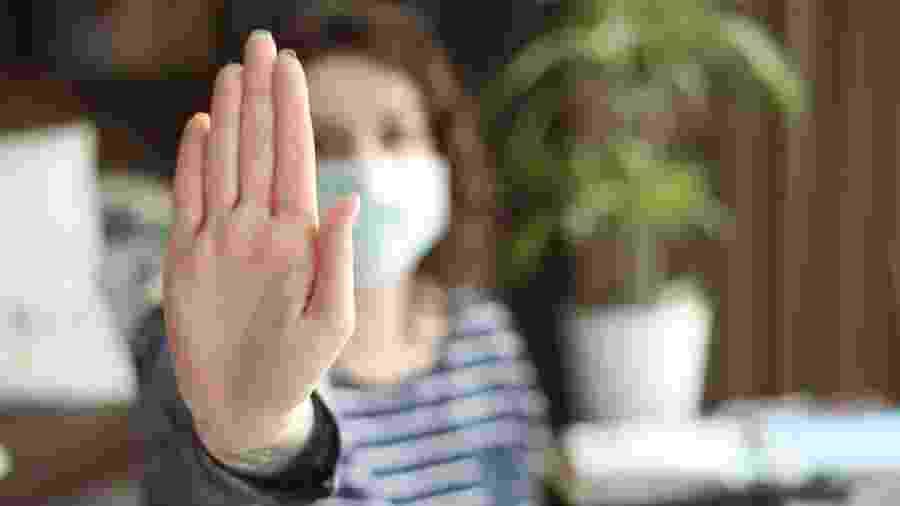 Mulher de máscara faz sinal contra a violência doméstica -