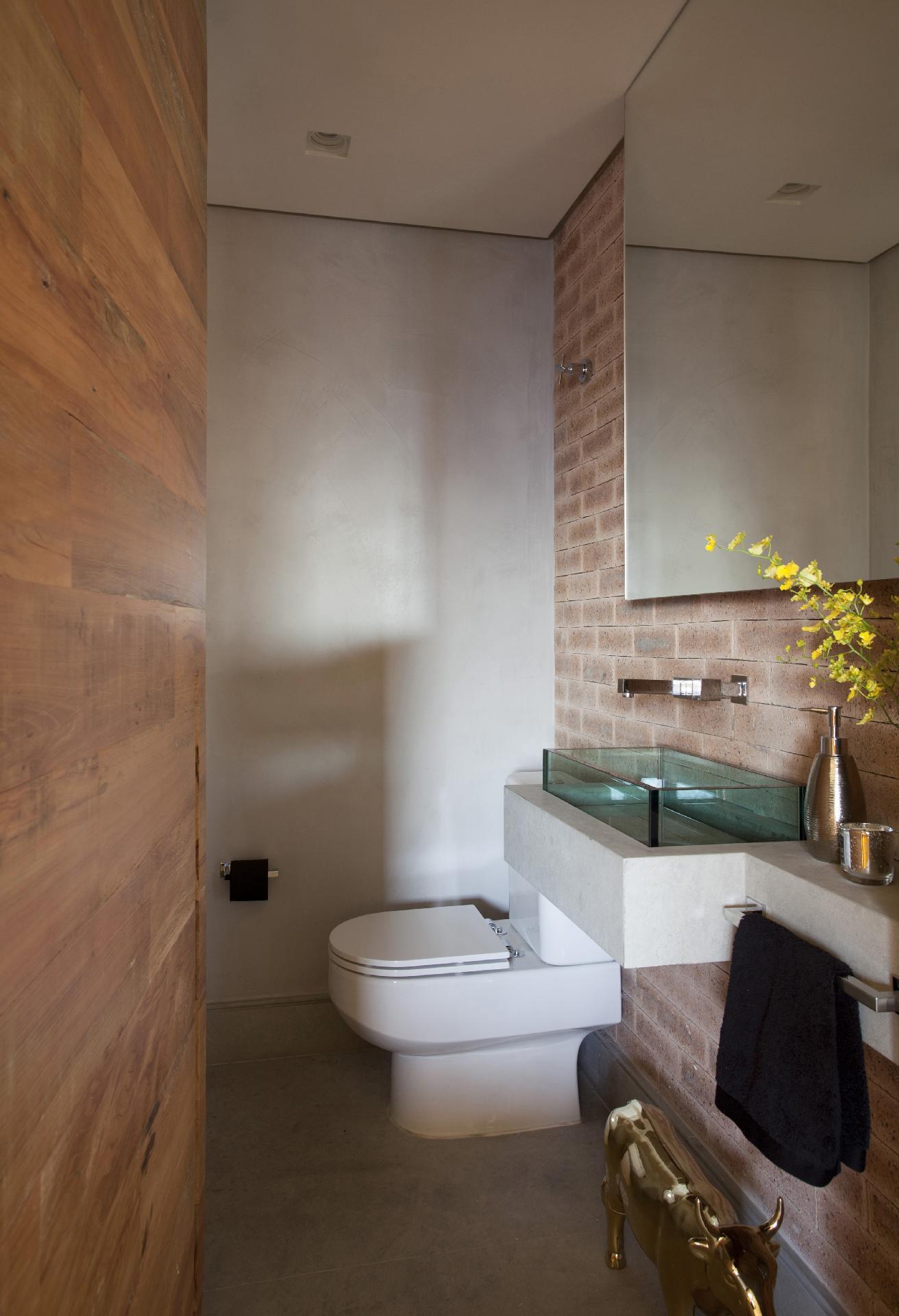 As paredes do lavabo no apartamento em São Paulo (SP), assim como parte das superfícies do 'living', foram revestidas com