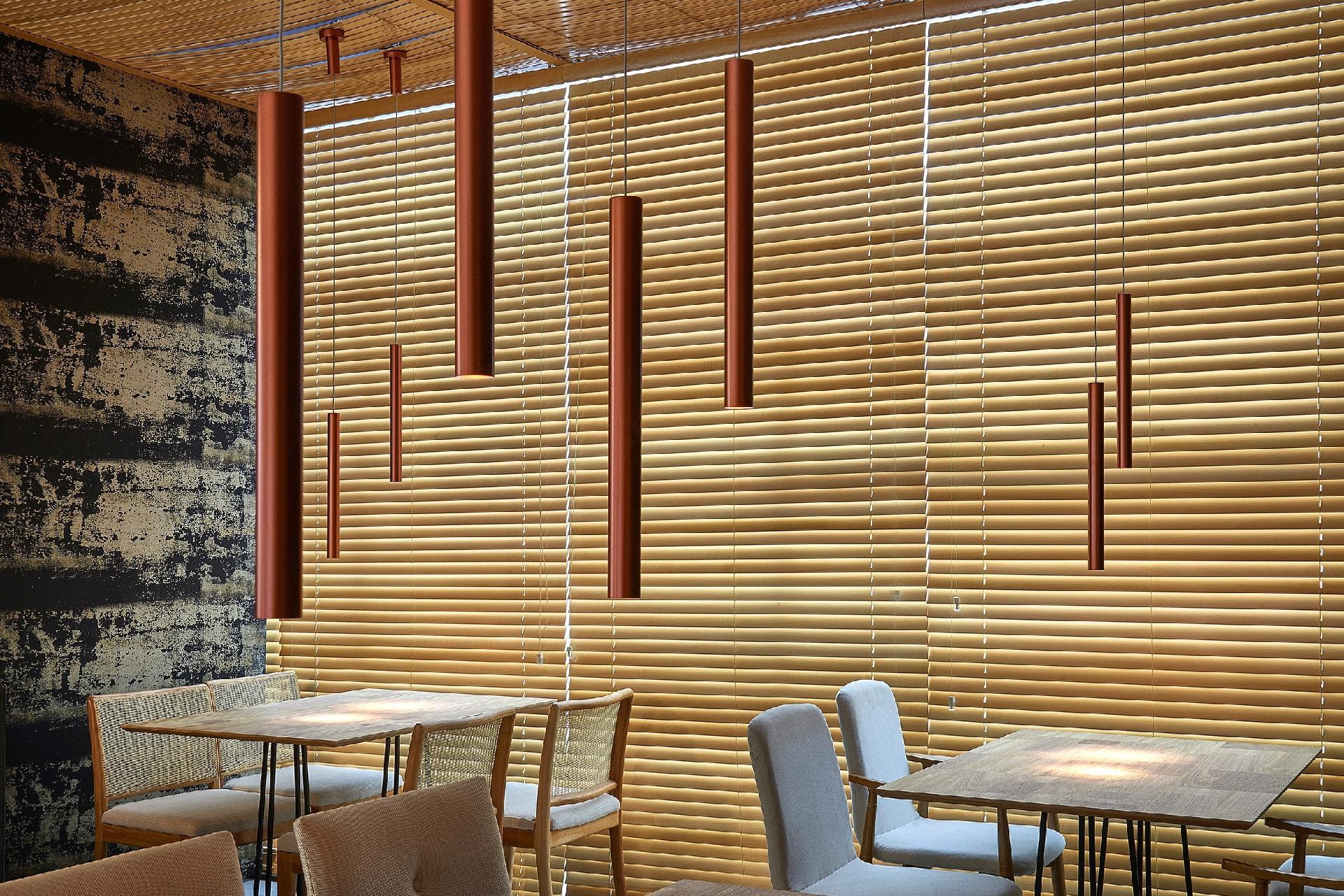 Casa Cor MG 2016 - O Restaurante, projetado por Du Leal e Eduardo Beggiato, combina saídas espertas para iluminar sem abrir mão do aconchego, que pode ser adaptada a uma sala de estar ou jantar. A estrutura do espaço é metálica e foi forrada internamente com persianas de madeira. Sobre as mesas, os pendentes modernos e minimalistas, estão pendurados em duas alturas e criam um belo movimento