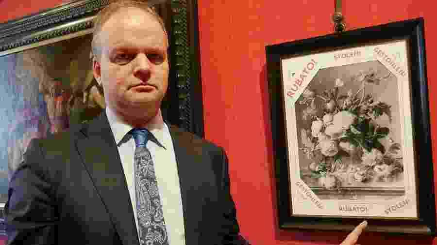 Diretor da galeria Uffizi, em Florença (Itália), Eike Schmidt posa ao lado de representação de obra roubada pelos nazistas - AFP PHOTO/ FLORENCE MUSEUM PRESS OFFICE