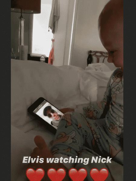 Elvis, filho do ator Nick Cordero, ri ao assistir a um vídeo do pai no celular - Reprodução/Instragram